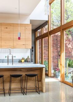 Beautiful wood cabinets....Light from garden through accordion doors. modern+open+clean lines kitchen. LOVE.