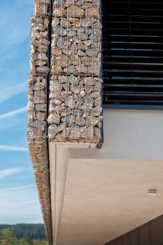 Gabion baskets filled with stone used as wall cladding.