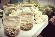 Słoiki ozdobione koronką, jutą, brzozowymi sercami, z dodatkiem kamyków jako wazony na kwiaty