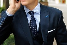 Navy suit, light blue plaid shirt, navy tie with dots