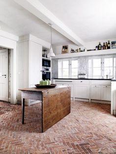danish modern design herringbone brick floor in a kitchen with center island for work prep, simple white color palette.