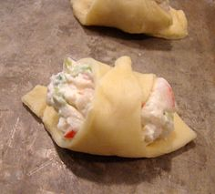 Crab Filled Crescent Wontons adp frm Pillsbury: 8 oz crescent rolls;   3 oz cr cheese, soft;   1/4 c mayo;   3/4 c cooked crabmeat, chop;   2 gr onions, chop;   1/8 cayenne pepper;   s  Oven 375°. Oil/spray cookie sheet. Unroll dough pinch seams, roll to rectangle. Make 24 squares. Mix oth ingred. Divide mix among squares, drop 1/2 in frm 1 corner of each square. Fold dough over filling, tuck end tightly under filling; Roll opp corner over; Seal. Brush w egg white. Bake 10-15 min til golden.