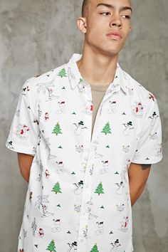 A holiday-inspired woven shirt in a slim fit featuring short sleeves, a buttoned front, a basic collar, a dolphin hem, and various Christmas-themed prints of snowmen, candy canes, reindeers, penguins, gingerbread cookies, and more.