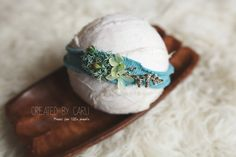 A beautiful teal headband, embellished with a mix of natural moss, flowers and grassesNewborn size