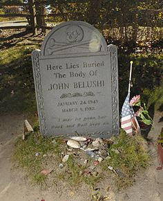 "John Belushi 1949-1982 ""I may be gone, but Rock & Roll lives on"" Buried in Martha's Vineyard, Mass. Belushi's tombstone was getting trashed so much his wife requested his body be moved to an unmarked plot some distance away from the tombstone."