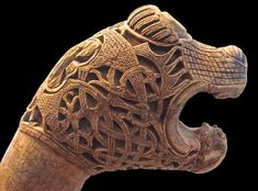 The wooden carving resembles a bear's head and is covered by a layer of intricately interlaced knotwork.
