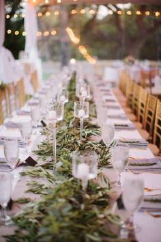 Add a touch of elegance by decorating the tablescape with a long green garland as a main wedding centerpiece.