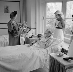 Queen Elizabeth chats to a patient and nurses in 49th Brigade Reception Hospital at Windsor, 18 March 1941.