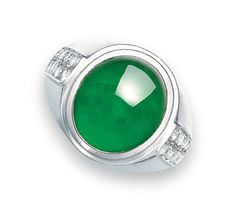 A JADEITE AND DIAMOND RING   Set with an oval jadeite cabochon of intense emerald green colour and very good translucency, to the brilliant-cut diamond shoulder, mounted in 18k white gold, cabochon approximately 15.5 x 13.5 x 6.8 mm, ring size 8¼. Price realized: 112,500 HKD (USD 14,561)