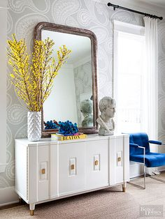 A lacquered midcentury sideboard and antique mirror follows the new-meets-old pairing formula. Paisley wallpaper wraps the dining room in pattern. Why We're Wowed: The large mirror, oversize wallpaper, and substantial accessories give the spacious, mostly neutral dining room a look-at-me attitude wtih dramatic scale./