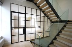A double height rear extension was added to this complete house renovation in central London. The house belonged to a noted British comedian and actor and was to receive a brand new contemporary redesign. Frameless Glass Balustrade, Glass Partition, Steel Frame Doors, White Interior Design, Roof Styles, Roof Architecture, Glass Floor, Roof Light, Roof Design