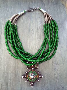 by Anna Holland | Antique Moroccan pendant from Tiznit with great enamel work still visible hangs from seven strands of old Venetian green whiteheart beads. Silver spacers from Africa, sterling silver cones, and sterling hook and eye clasp | Sold