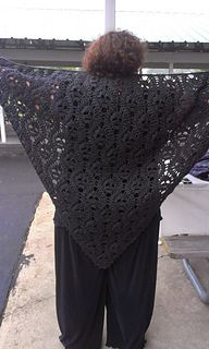 """Seeing so many skull shawl patterns lately that are an open kind of lace work made me wonder if there wasn't some other way to present this popular motif. Then it occurred to me to use a tessellating setting, and after a bit of trial and error the shawl with the look of """"lost souls"""" developed. My thanks to Linda for modeling the finished shawl (glad you enjoyed your birthday present)!"""