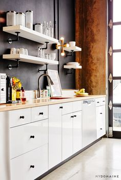 Office kitchen with black walls, white shelves, white cabinets, wood countertops, and gray floors