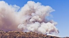Fire Season.  Plumes of smoke rise above the hills as a brush fire rages.