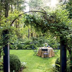 """Living """"walls"""" made of boxwoods, hostas, and hydrangeas create a cozy and secluded outdoor dining room."""