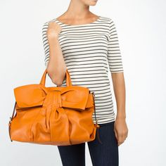 Love this orange purse with a bow!