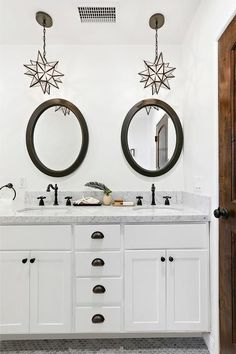 A bronze and white bathroom featuring glass Moravian Star Pendants decoratively hang over a bathroom sink with oil rubbed bronze vintage faucets and carrera marble countertops.