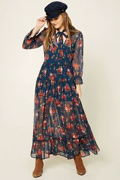 A semi-sheer woven maxi dress featuring an allover floral print, a self-tie mock neckline, a front keyhole detail, long sleeves with elasticized bell cuffs, a ruffled waistline, tires with ruffle details, and a mini cami slip with adjustable straps.