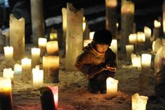 A child looks at a candle flame during an event to pray for the reconstruction of areas devastated by the March 11, 2011 earthquake and tsunami, in Iwanuma in Miyagi prefecture, an area hit by the disaster, in this photo taken by Kyodo January 11, 2012.