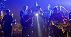 Police congregate outside the home Wednesday, Aug. 28, 2013. A man and woman are dead and a Gwinnett County police officer is on administrat...