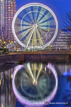 Reuzenrad The View op de Binnenrotte in Rotterdam, naast de bibliotheek en de Markthal, spiegelend in de Steigergracht. - Ferris Wheel the View on the market square in downtown Rotterdam, next to library and market hall, reflecting in a canal.