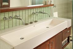 he backsplash behind the sink is a glass tile in a 1x4 dimension. You can find similar at modwalls.com. The shower tile Dal Tile P-Zazz in Gray Shimmer.