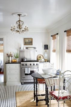 A chandelier, an oil painting, and floor-length draperies in a kitchen? Yes! Janet, a former chef, chose to dress up her 100-square-foot space in a way that feels in keeping with the rest of the home.