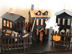 haunted houses made with the Winter Wonderland cartridge for Cricut. Not only does it have a cool font and some fun wintery pictures, but it cuts out the pieces to construct AN ENTIRE VILLAGE. A little black glitter paint, a little orange paper, a couple pre-made accents, and VOILA! we made our own sparkly Halloween village. The houses I put together in the evening and the girls helped me paint the base board, the fences, and glue on the accents.