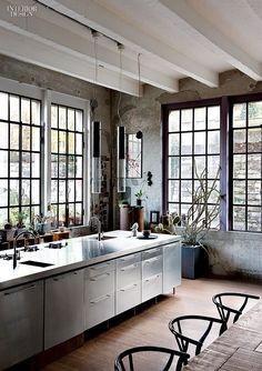 Industrial (converted factory) style kitchen with a touch of vintage charm. Vaulted ceilings with beams painted white give it a bit of an old farmhouse style look. Lovely! #industrialkitchendesign #industrialfarmhouse #industrialcountrykitchen