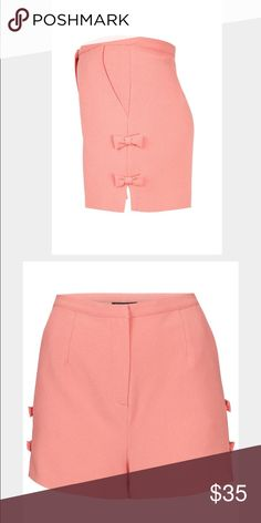 """Topshop side bow pink shorts Super cute slightly high waisted shorts from Topshop. Coral pink color. Size UK12 or US 8. Slant pockets. Flat front with zipper. No condition issues, only worn once or twice. Lined. Poly/elastane/acetate. Length down side is 13"""". Waist is about 15.5"""" flat. More pics to come! Topshop Shorts"""