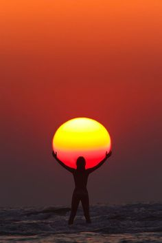 "Picture of the Day: Praise the Sun. ""In this perfectly timed sunset capture by Anton Jankovoy, we see the silhouette of a woman appearing to hold/praise the sun. The photo was taken in July of 2011 at Paradise Beach in Maharashtra, India. To get the shot Anton used a FL 600mm at 1/250 sec, f/11, ISO 200. """