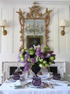 Gilt mirror over the fireplace flanked by sconces, reflection of chandelier, purple tablescape and centerpiece of hydrangeas and lilacs - Carolyne Roehm