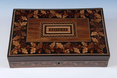 A Tunbridge Ware games box with the word 'Besique' in mosaic and with a border of oak leaves and acorns. The interior has rules for Besique and four packs of De La Rue cards. Attributed to Henry Hollamby. This box, and other items of Tunbridge Ware, is offered by Amherst Antiques at The Edenbridge Galleries, Kent. http://www.edenbridgegalleries.com