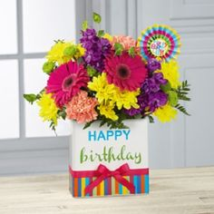 """FTD Birthday Brights Bouquet - BD2 - is a celebration of color to surprise and delight your recipient on their big day! Hot pink gerbera daisies, orange roses are surrounded by purple gilly flowers, yellow mums, orange carnations, green button poms, bupleurum, and lush greens. Presented in a rectangular ceramic vase with colorful striping at the bottom, """"Happy Birthday"""" lettering at the top, and a pink bow at the center, and accented with a striped birthday pick to create a festive gift."""