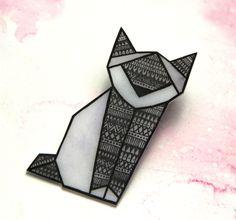 Origami Brož jako kočičí origami. Je vyrobena z plastu,její odstín přechází přes šedou k jemně fialovošedé a je pokreslená drobnými motivy. Jako bájná sfinx bude chránit Vaše klopy. Brož se přípíná malým brožovým můstkem, je vysoká cca 6 cm.