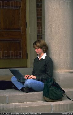 Female college student sitting outdoors using a laptop computer. - stock photo