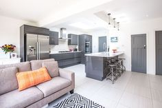 Single-storey kitchen extension to 1930s house in Long Ditton by L&E (Lofts and Extensions) - don't move extend. Grey Kitchen, Glossy Kitchen, Skylights, Patterned Tiles, Grey Internal Doors, Monochrome Rug, Industrial-style Bar Stools