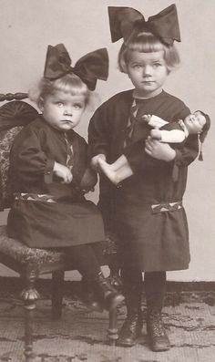 Vintage photo of two little girls with large bows in their hair. On the right, she is holding a doll.