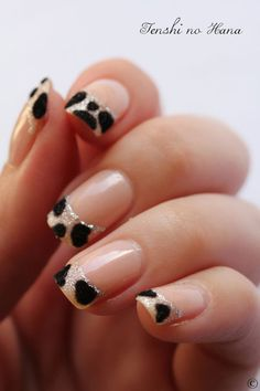 Leopard inspired French tips all the way! The nails are coated with clear polish as base and tipped with an almost cream to clear polish. Atop are silver glitters for accent and small swabs of dark fur like accents are formed to create the leopard prints.