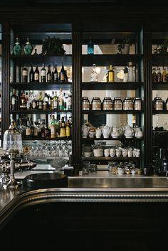Jars, tea/coffeepots next to liquor, silver, mirror and black. Caffè Propaganda | Rome
