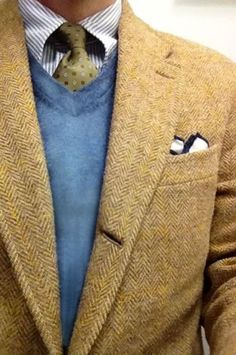 Tan colored herringbone tweet jacket paired with blue V-neck sweater, floral tie in olive, striped shirt, and pocket square