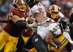 Washington Redskins defensive lineman Kedric Golston (L) grabs the jersey of Baltimore Ravens running back Ray Rice (R) in the second half of their NFL football game in Landover, Maryland December 9, 2012. REUTERS/Gary Cameron (UNITED STATES - Tags: SPORT FOOTBALL)