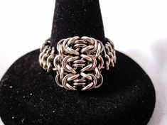 """By hand-weaving almost 200 super-tiny jump rings (1-2mm diameter), this beautiful mesh ring features 3 """"byzantine"""" chainmaille units, connected to a european 4-1 band that forms the rest of the ring.    Amazingly comfortable to wear.  Available in two different designs: silver, and silver with ..."""