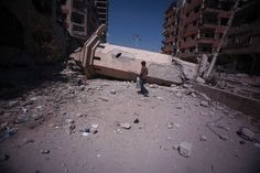 A Syrian boy walks past the collapsed minaret of a mosque in the rebel-held city of Douma, Syria.