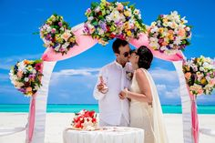 Pink and white wedding arch decorated with tropical flowers. Juanillo beach, Dominican Republic. Organization by Caribbean Wedding. Photo by Nik Vacuum.