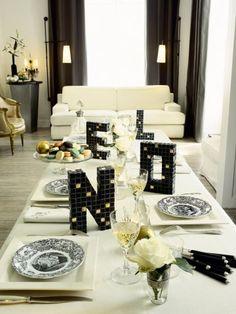 Des lettres en tasseau de bois recouvertes de mosaïque noir et de carrés dorés sur la table de Noël
