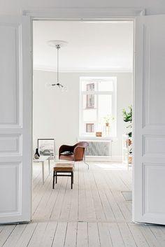 un intérieur typiquement scandinave : un plancher en bois peint en blanc, des murs blancs et du mobilier design