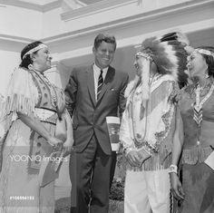 """Meeting the President. Washington: President Kennedy met with representatives of 90 American Indian tribes at the White House today and was presented with the Declaration of Indian Purpose. During the ceremony, Kennedy described the American Indian as the """"First Citizen"""" and said all Americans have a strong obligation to improve the living conditions of the Indians. (Left to right) Eleanor Red Fawn Smooth, Mohawk-Cherokee Tribe, Connecticut; Kennedy; and Calvin W. McGhee, Atmore, Louisiana."""
