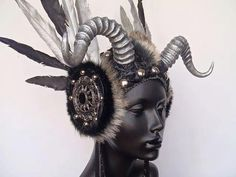 Hand-made faux feather and horn headpiece created to order. This headdress is unisex and can be worn by a man or woman. Your custom piece can made in a similar color scheme or we can mix it up in any way your lil heart desires! (SEE GOLD FAUX FEATHER EXAMPLE).  You can choose the color of your horns, metal discs, fur and feathers. .Please shoot me a message to discuss the possibilities. Attaches to the head with an elastic strap on the underside. Horns are made by my friend at Faust & Co…